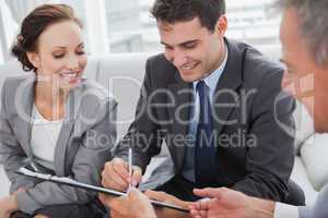 Businessman signing contract while his partner is looking at him