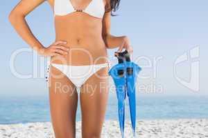 Perfect female body in white bikini holding fins