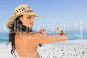 Attractive brunette with straw hat putting on sun cream