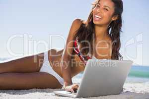 Happy attractive young woman in bikini with her laptop