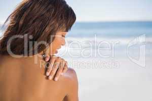 Pensive woman applying sun cream on her shoulder