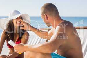 Handsome man applying sun cream on his girlfriends nose