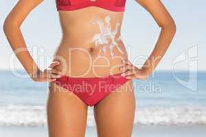 Fit woman body with sun cream on belly