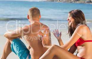 Cheerful attractive woman applying sun cream on her boyfriends b