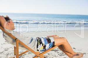 Handsome man lying on his deck chair admiring sea