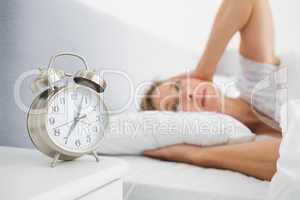 Blonde woman covering her ears from alarm clock noise in bed