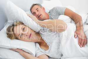 Irritated wife blocking her ears from noise of husband snoring