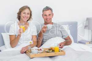 Smiling couple having breakfast in bed together