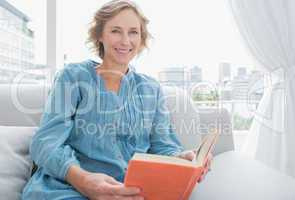 Content blonde woman sitting on her couch holding a book