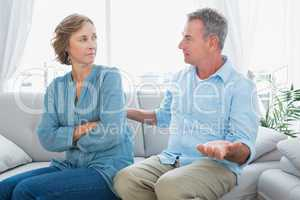 Middle aged couple sitting on the sofa having a dispute