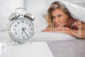 Annoyed blonde staring at her alarm clock