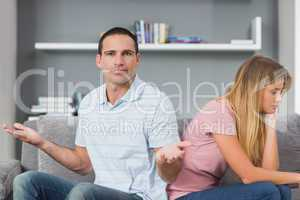 Couple sitting back to back after a fight on the couch with man