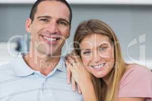 Happy couple sitting on the couch smiling at camera