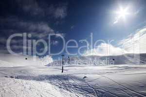 ski slope, gondola lift and blue sky with sun