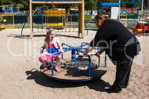 dad rolls his daughter on a small carousel