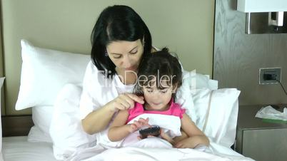 Mother teaching her little Daughter to play in the mobile
