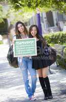 Mixed Race Female Students Holding Chalkboard With Teamwork and