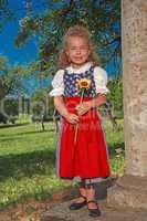 kleines Bayerisches Mädchen im Dirndl mit Sonnenblume
