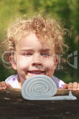 Lächelndes kleines Mädchen mit schönen lockigen blonden Haaren