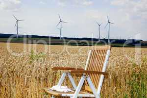 Garden chair in front of the corn field with windmills