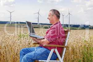 Man with laptop in cornfield
