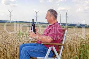 Man sitting with wine bottle in cornfield