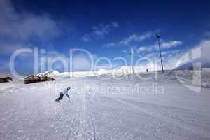 hotel in winter mountains and snowboarder on slope