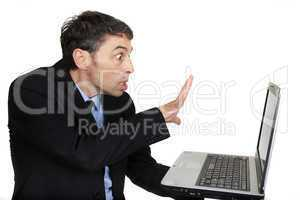 Businessman casting a spell on his laptop