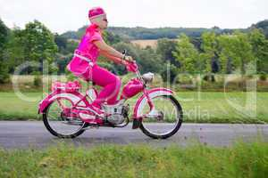 Woman rides on pink scooter