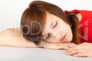 Die junge Frau liegt schlafend auf einem Tisch