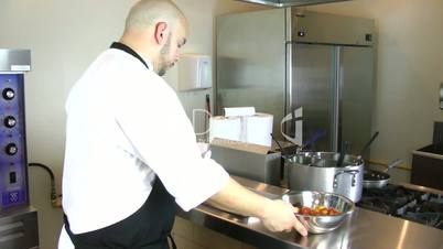 chef putting baking pan with tomatoes into oven