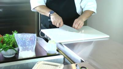 Cropped view of the hands of a man slicing a mushroom with a kitchen knife on a chopping board