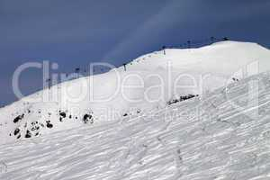 Off-piste slope and ropeway against blue sky