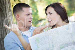 Lost and Confused Mixed Race Couple Looking Over Map Outside
