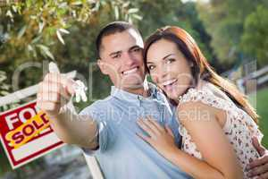 Military Couple with House Keys and Sold Real Estate Sign