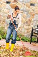 Smiling woman raking leaves fall housework garden