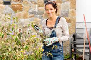 Happy woman clipping bush garden hobby clippers