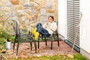 Happy woman relaxing autumn patio drinking tea