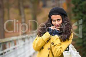 Young woman standing autumn park yellow coat