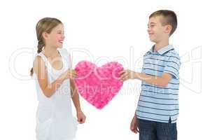 Smiling children holding heart shaped soft toy