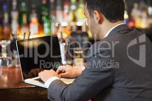 Handsome businessman working on his laptop while having a drink