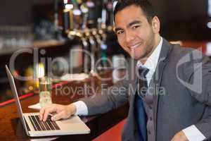 Smiling businessman working on his laptop