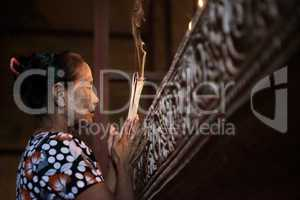 Asian woman praying with incense sticks