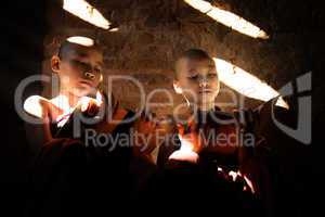 Two Southeast Asian little monks reading book