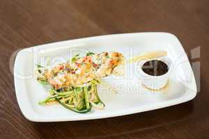 Asian inspired fish dish with noodles and julienne vegetables