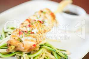 Asian fish dish with noodles and julienne vegetables