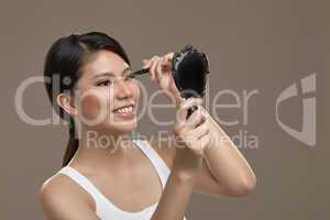 female asian applying eye liner with mirror