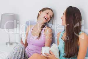 Pretty friends chatting over coffee in bed