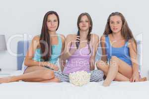 Girls sitting on bed at sleepover