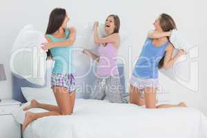 Girls in bed having pillow fight in pajamas